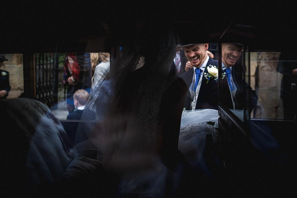 groom helping bride into vintage car