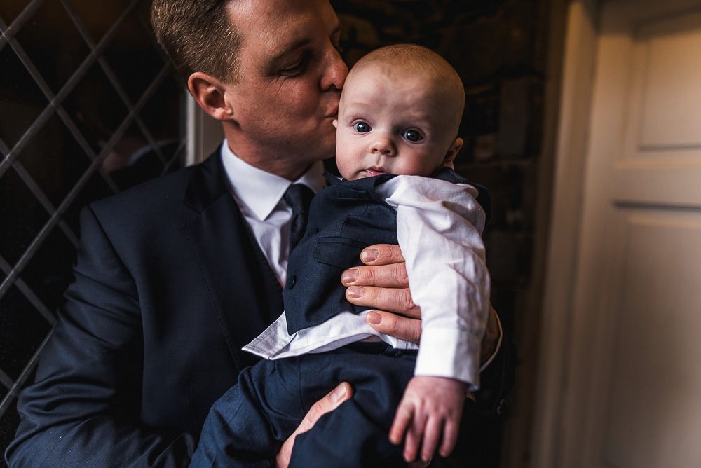 groom kissing baby