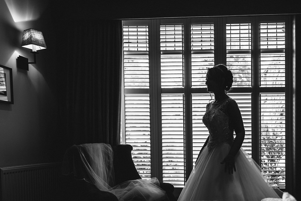 bride silhouetted against window
