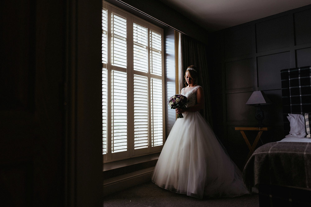 Bride stands at large window at Mitton Hall wedding