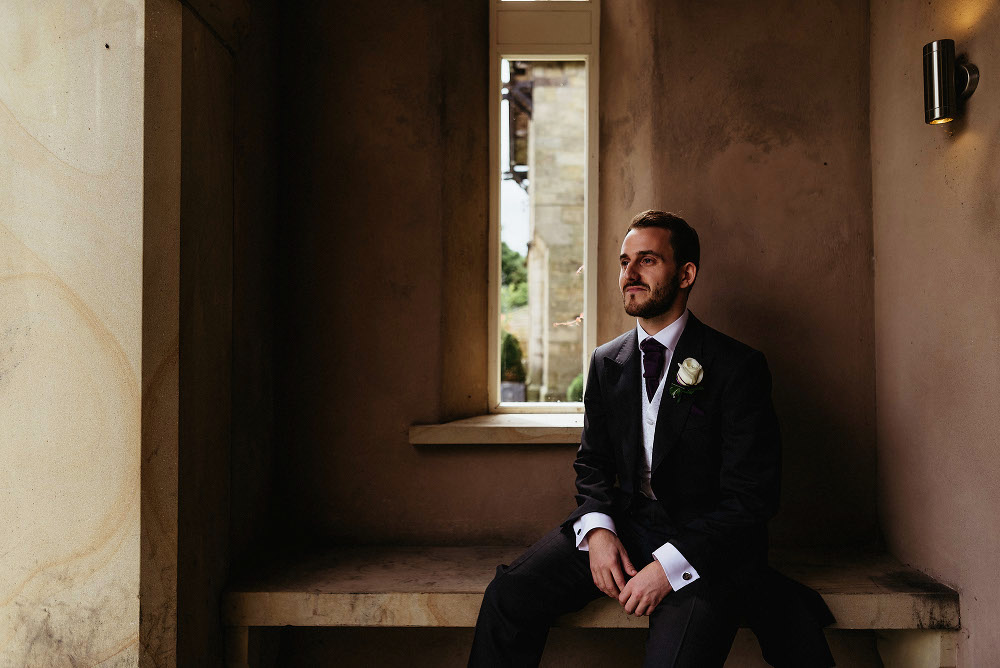 groom sitting outside Mitton Hall