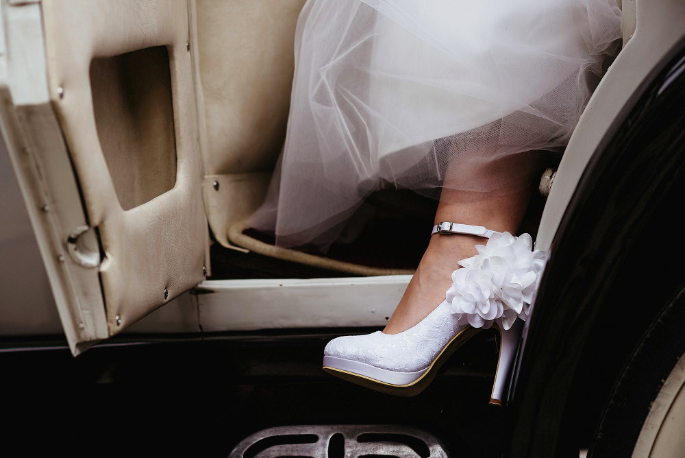 white wedding shoe stepping out of car