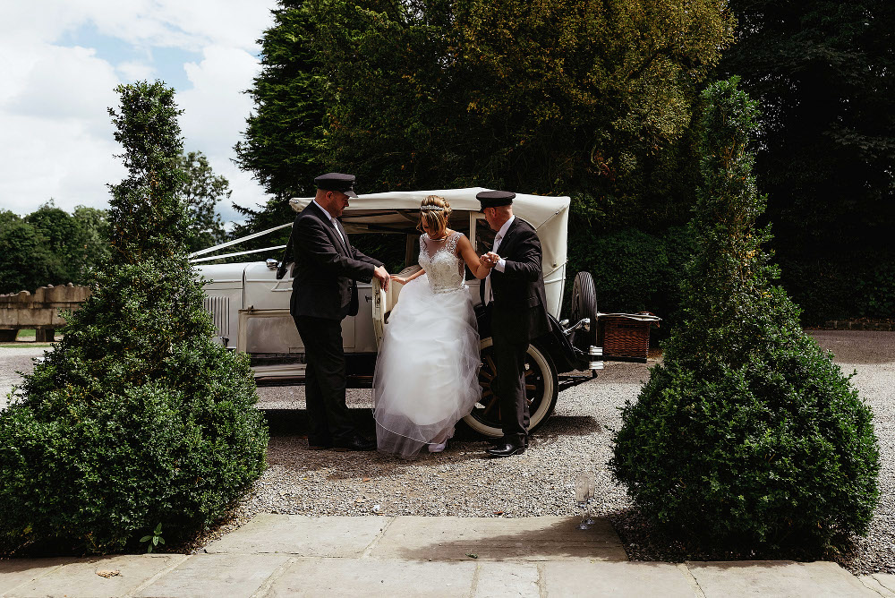 bride is helped out of vintage wedding car