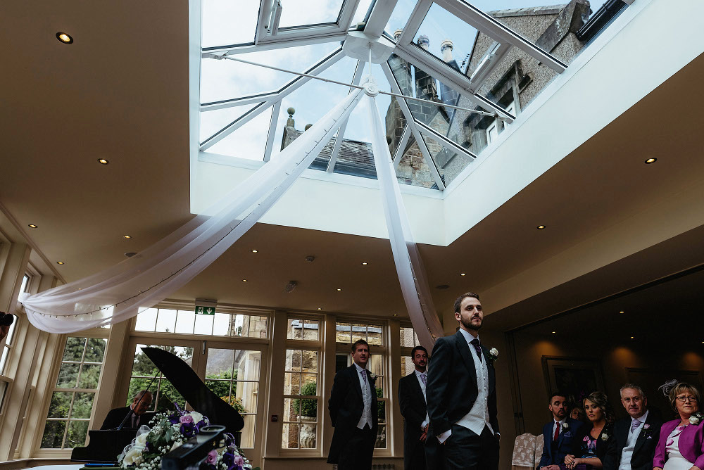 groom waits under glass roof in ceremony room