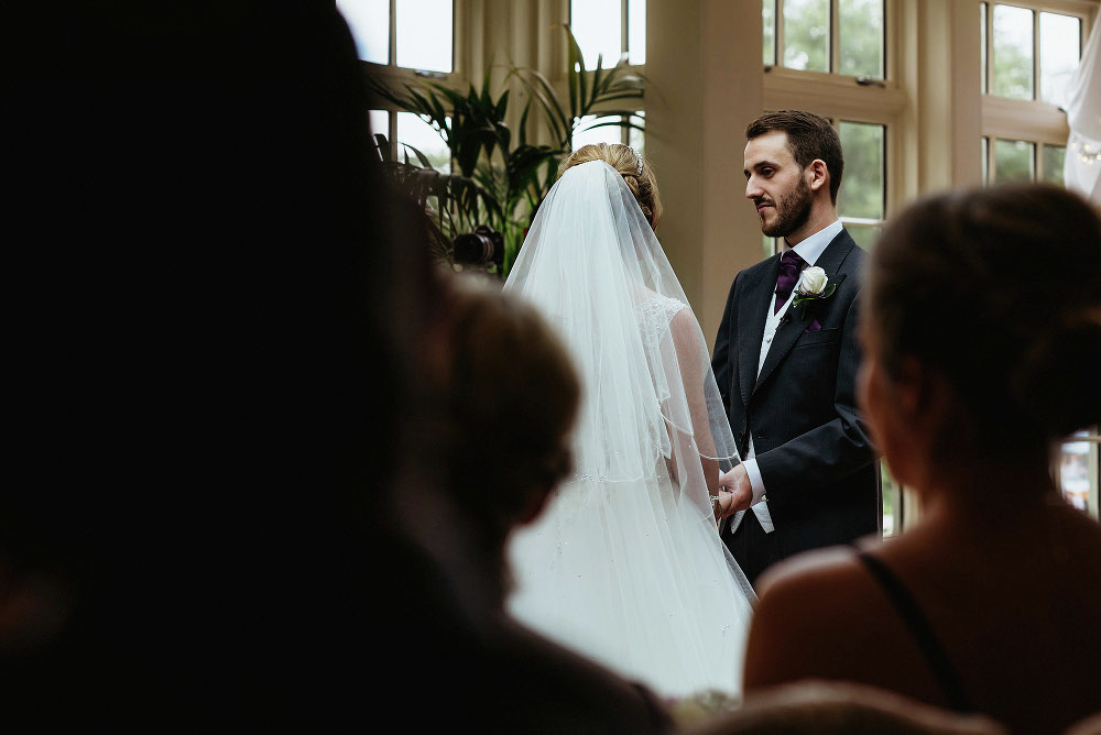 groom looks at bride during ceremony