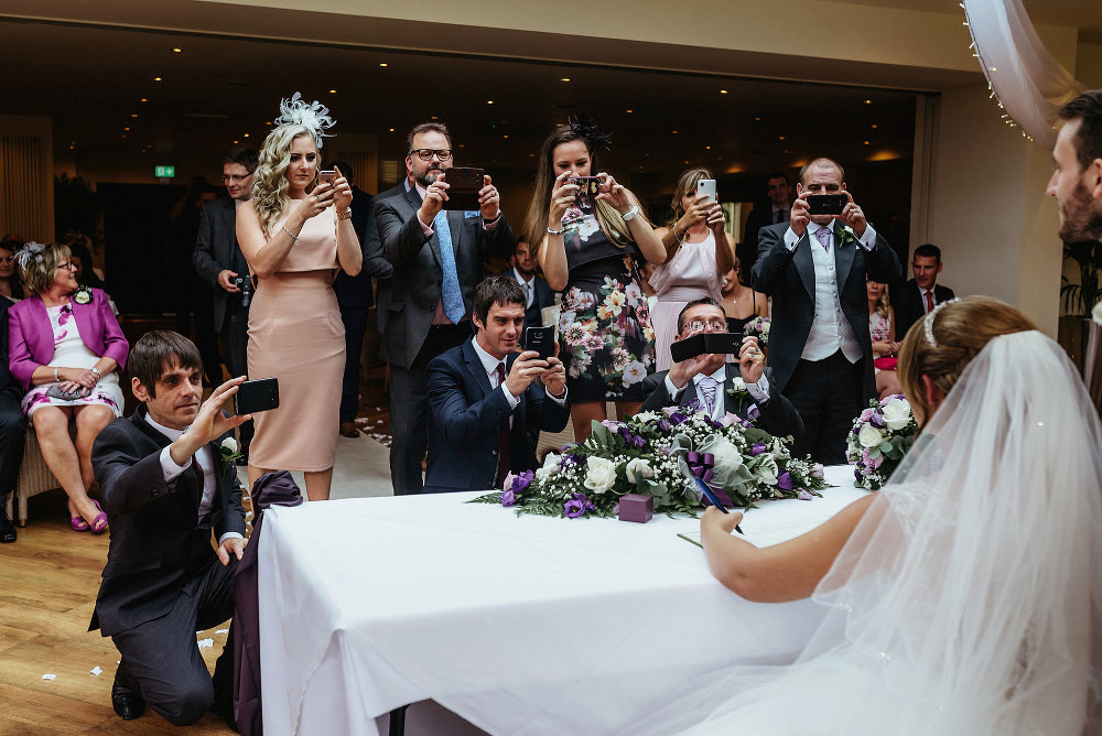 eight guests with mobile phones take photo of newlyweds
