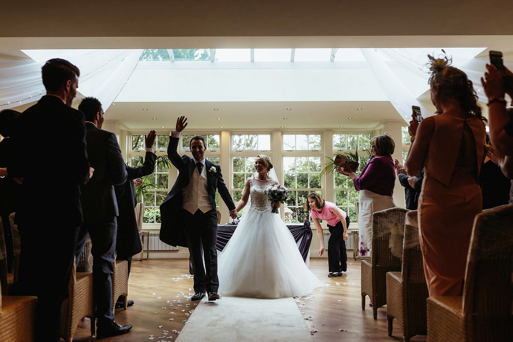groom raises hand as couple leave ceremony