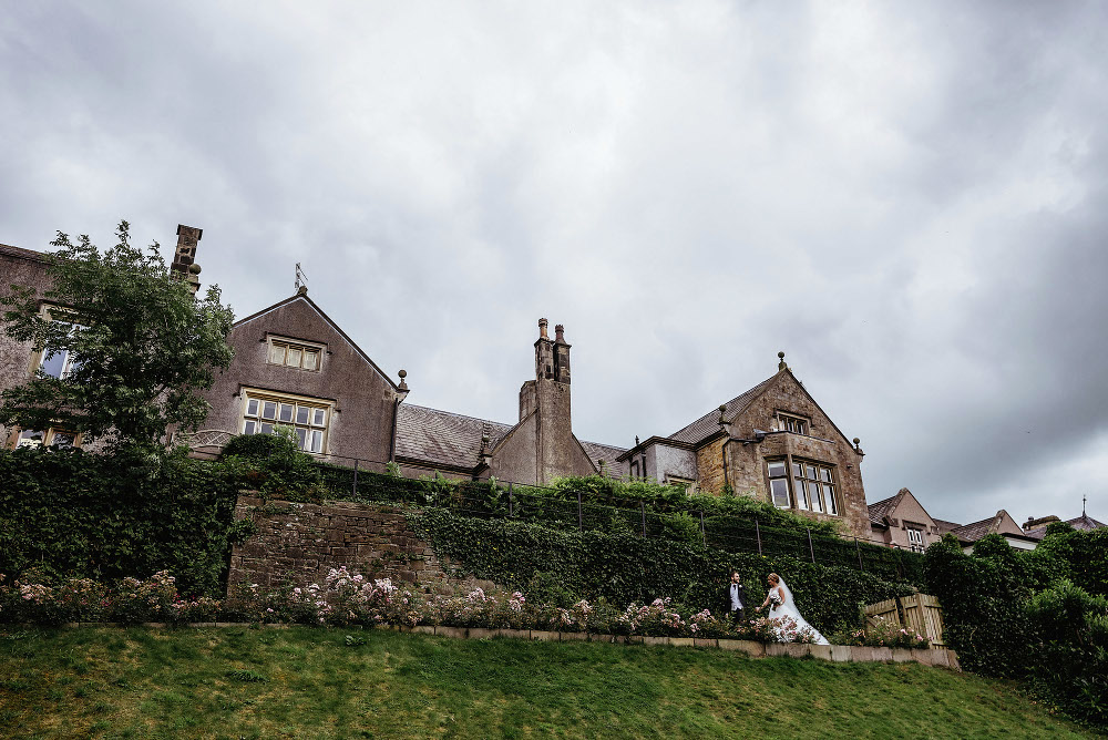 Bride and groom holding hands outside Mitton Hall hotel