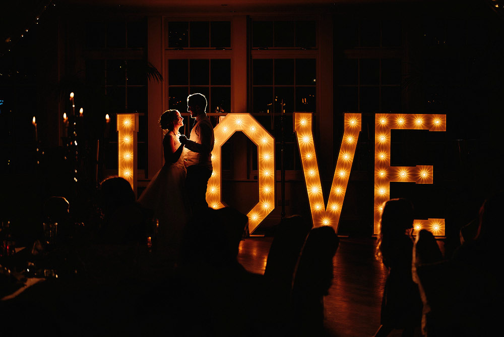 bride and groom dancing in front of illuminated letters
