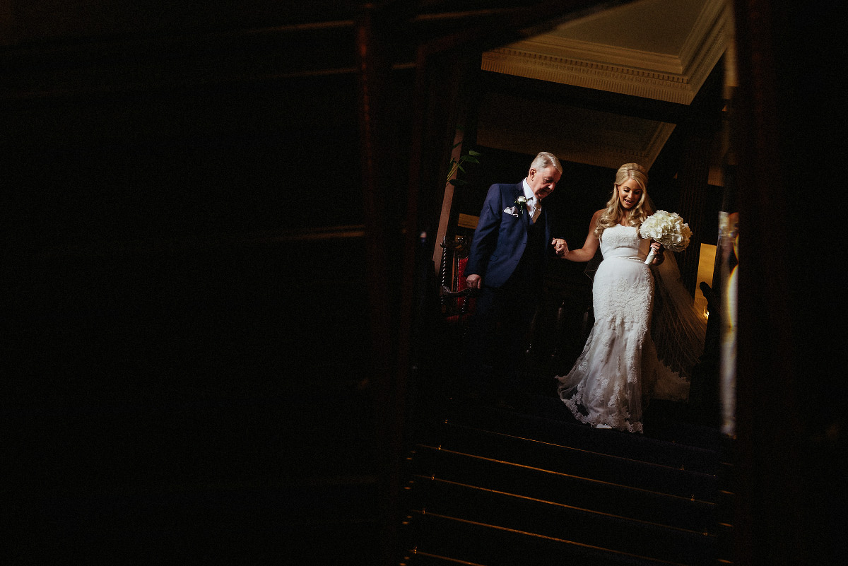 bride and dad walk down stairs at Eaves Hall