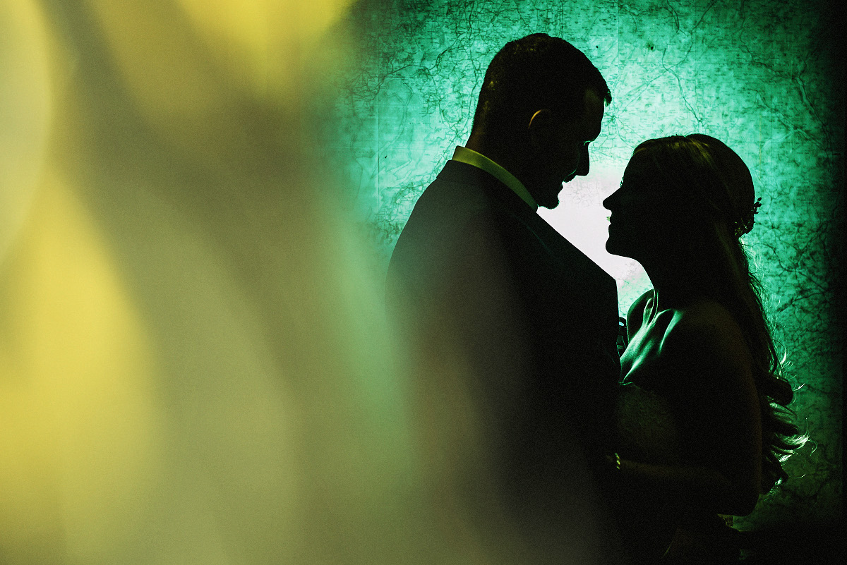 bride and groom silhouetted against green background with yellow lights on left