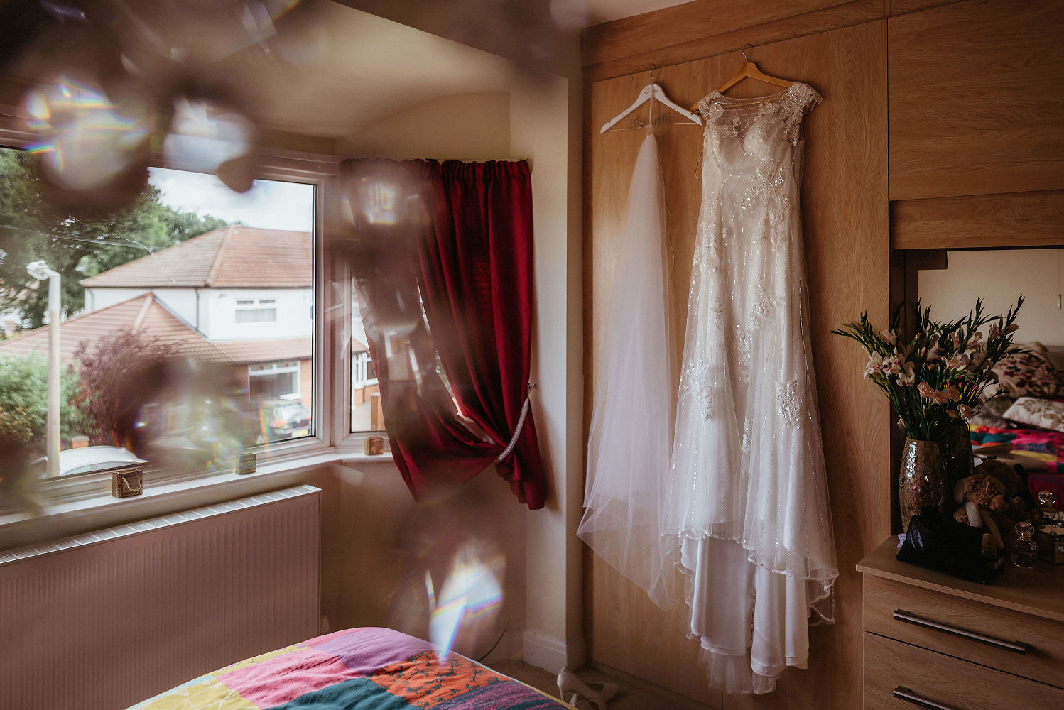 wedding dress hangs in bedroom