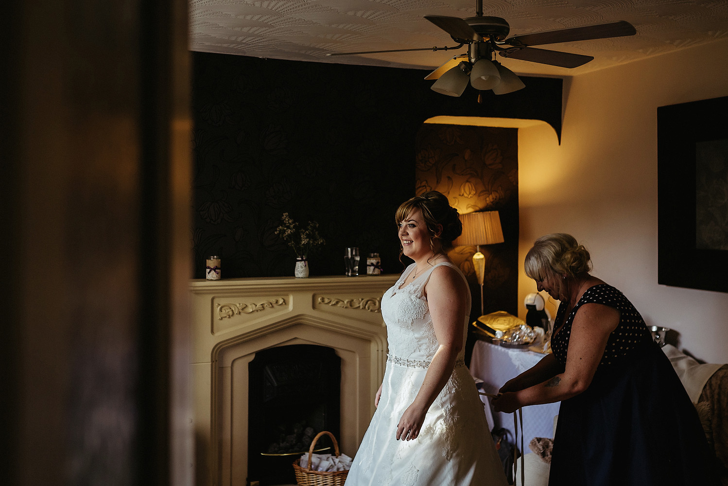 mum helps bride into dress