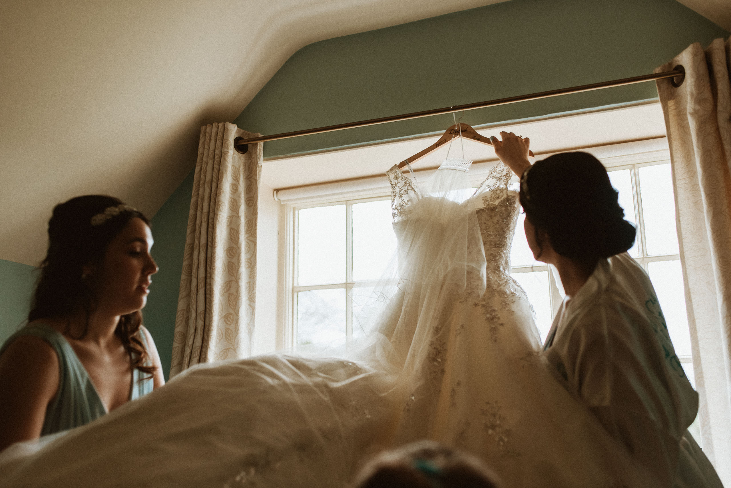 bride takes down flowing wedding dress from curtain rail
