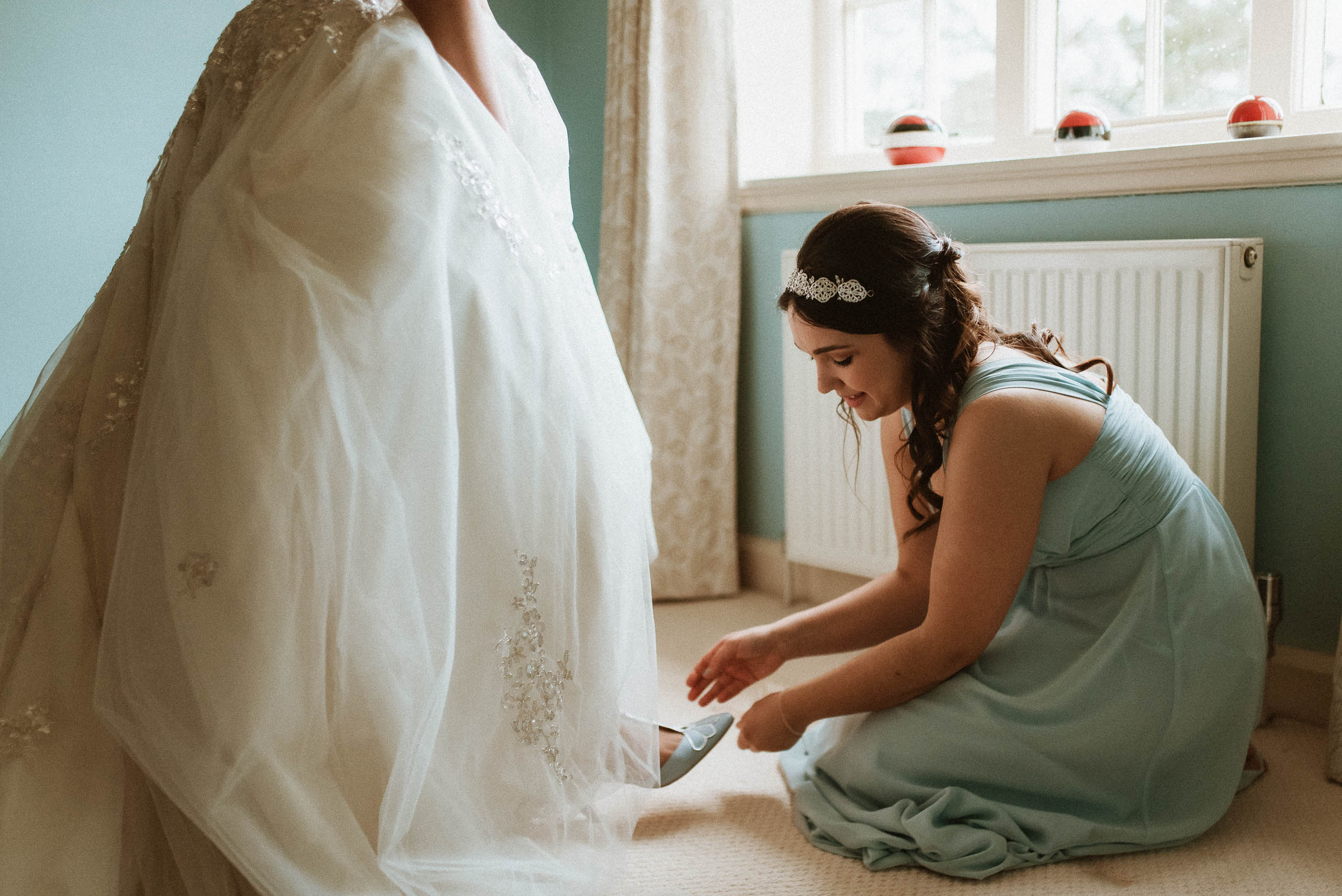 bridesmaid helps bride with her blue shoes