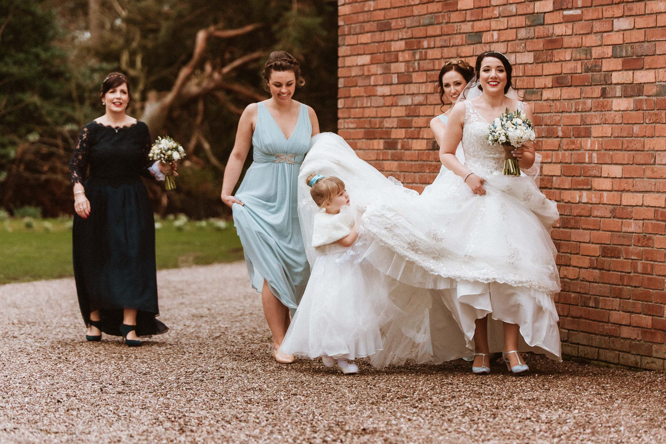 flower girl helps bride with dress