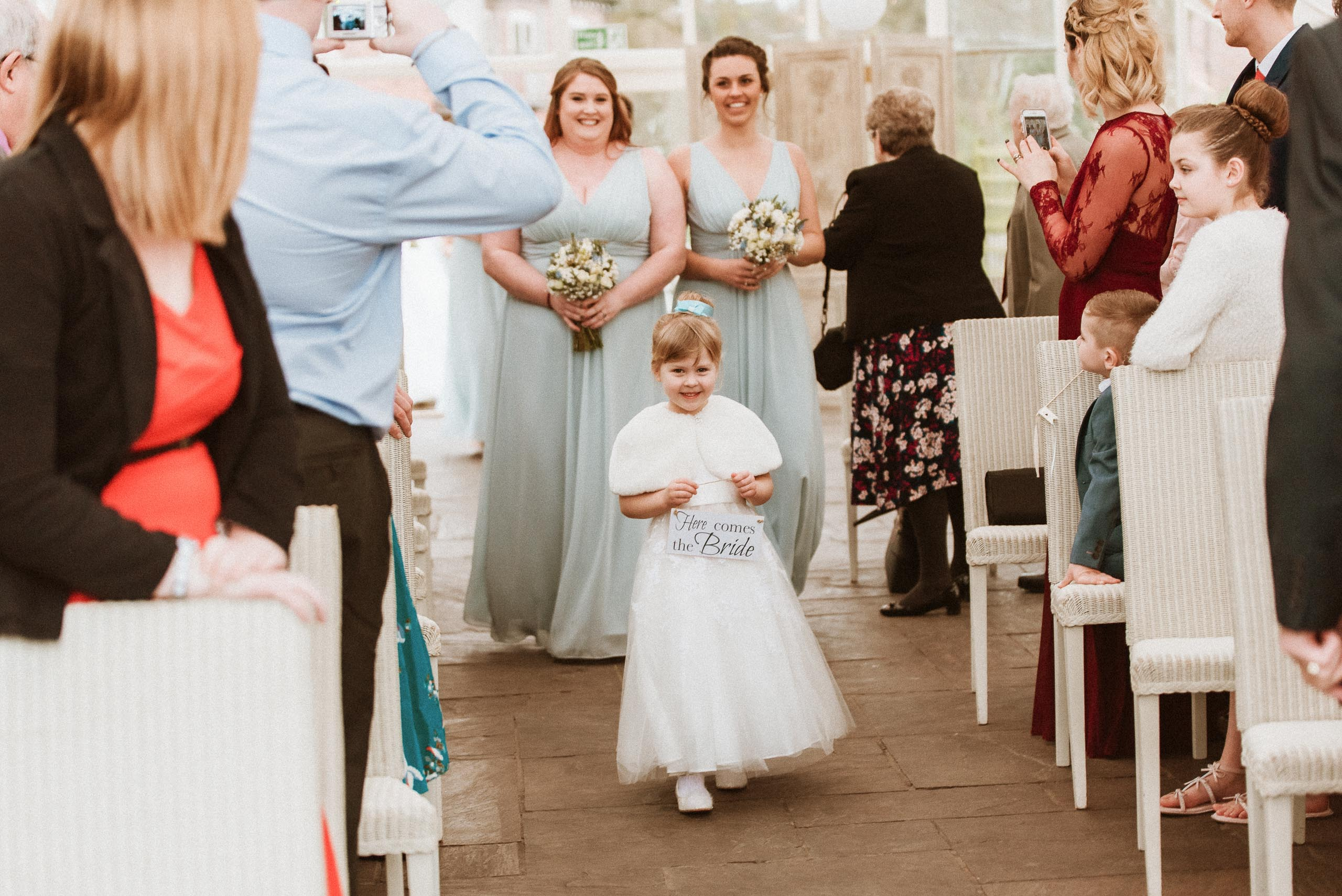 """flower girl walking up aisle holding sign that reads """"here comes the bride"""""""