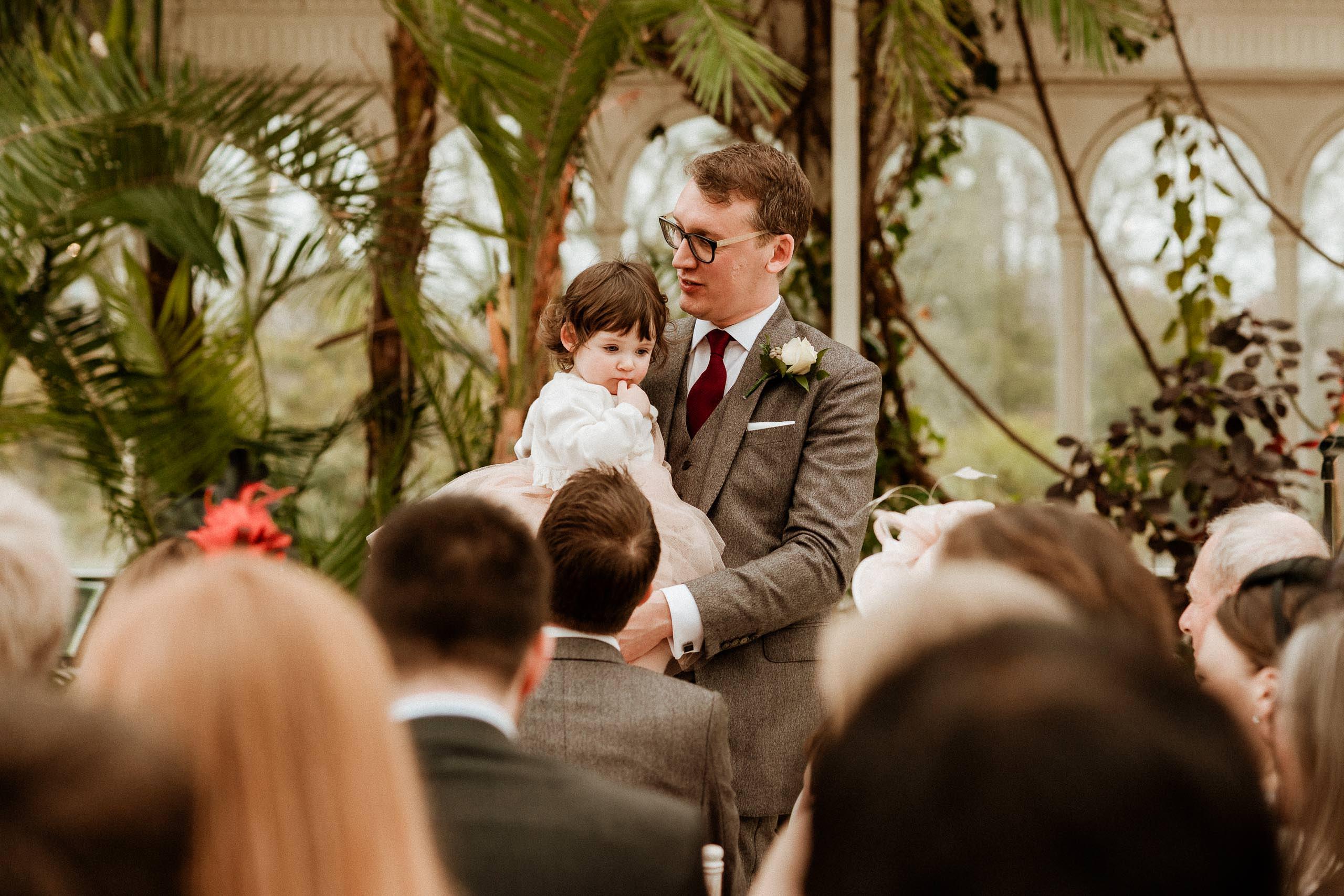 groom holds flower girl