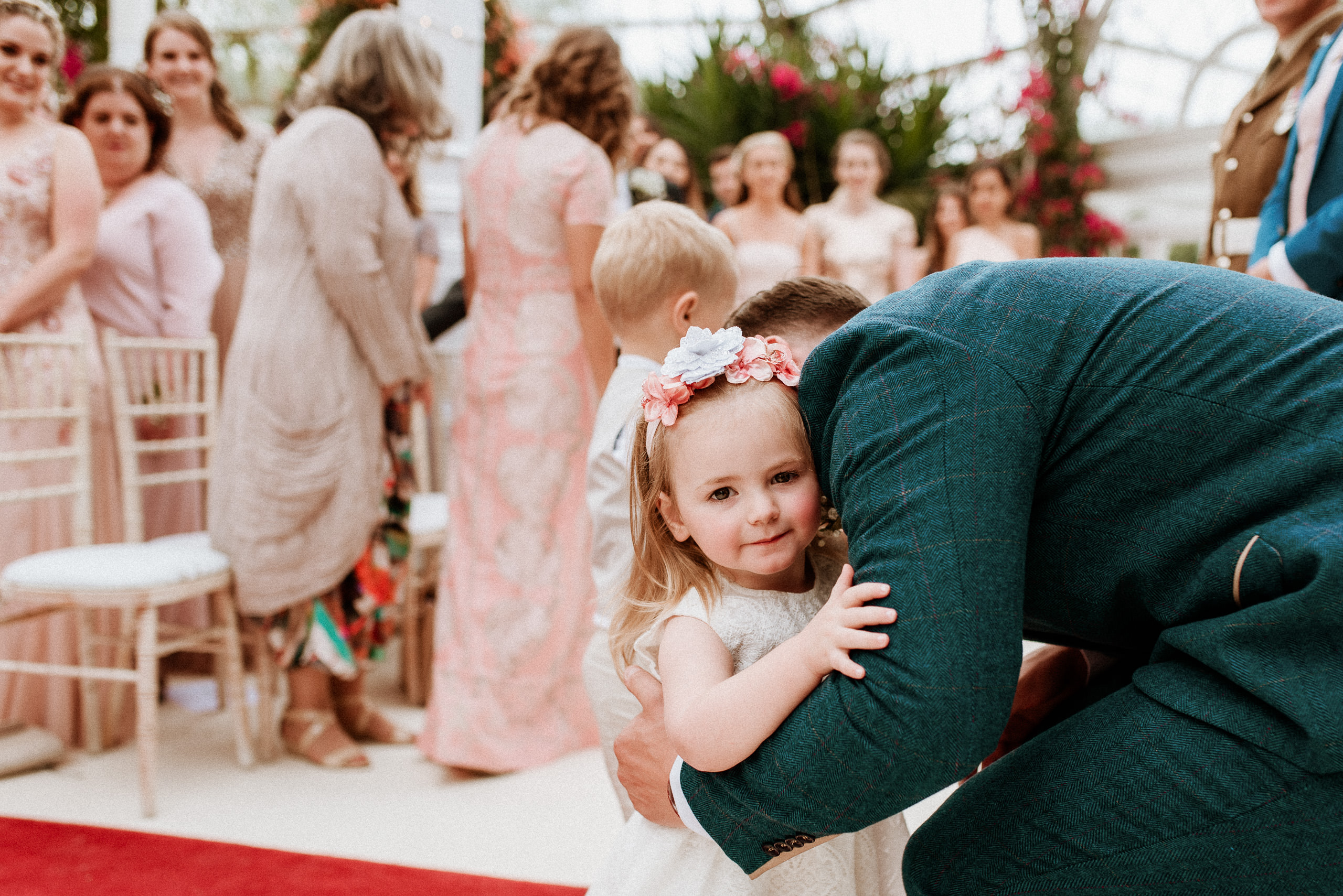 groom crouches to hug a young flower girl