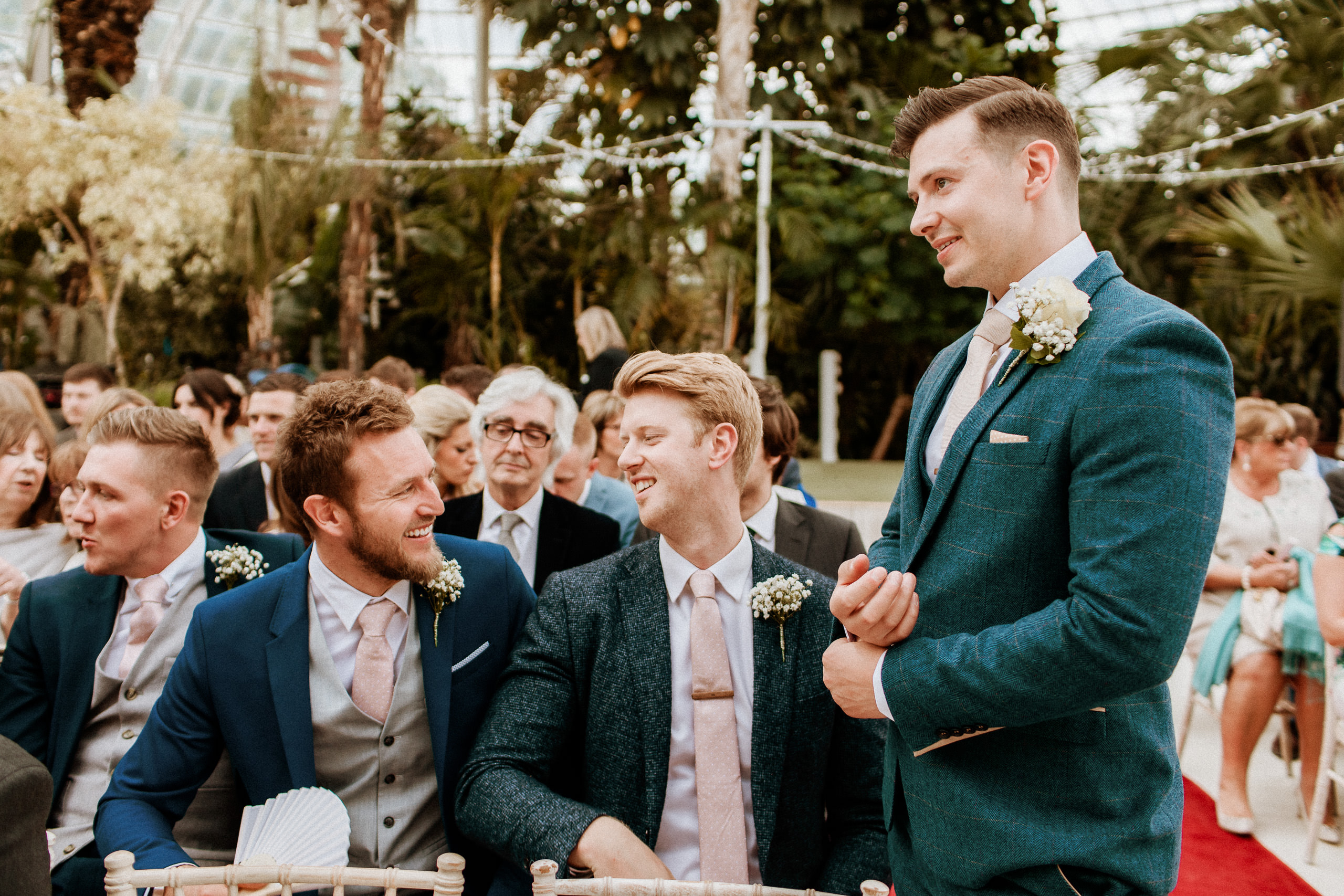 groom stands and laughs with his groomsmen