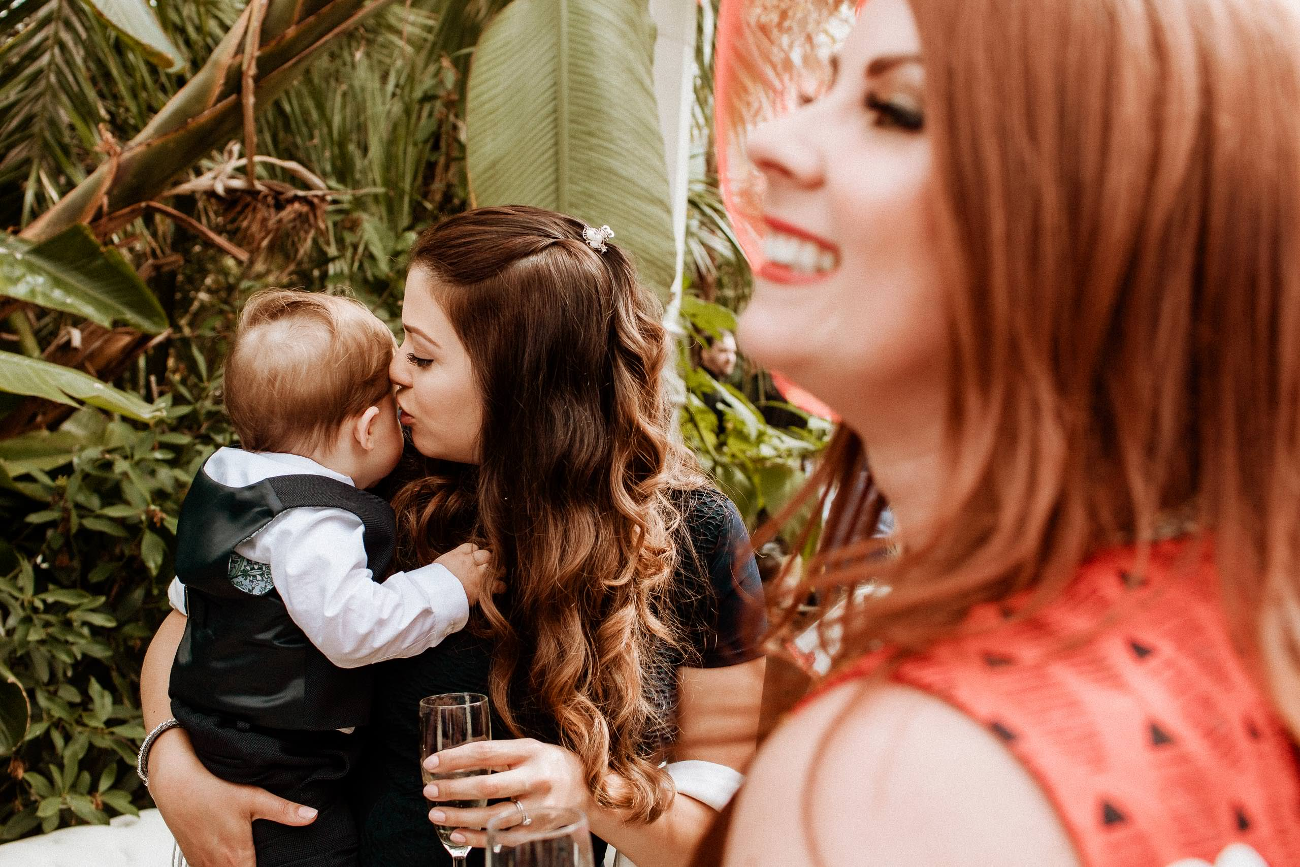 wedding guest holding and kissing her child
