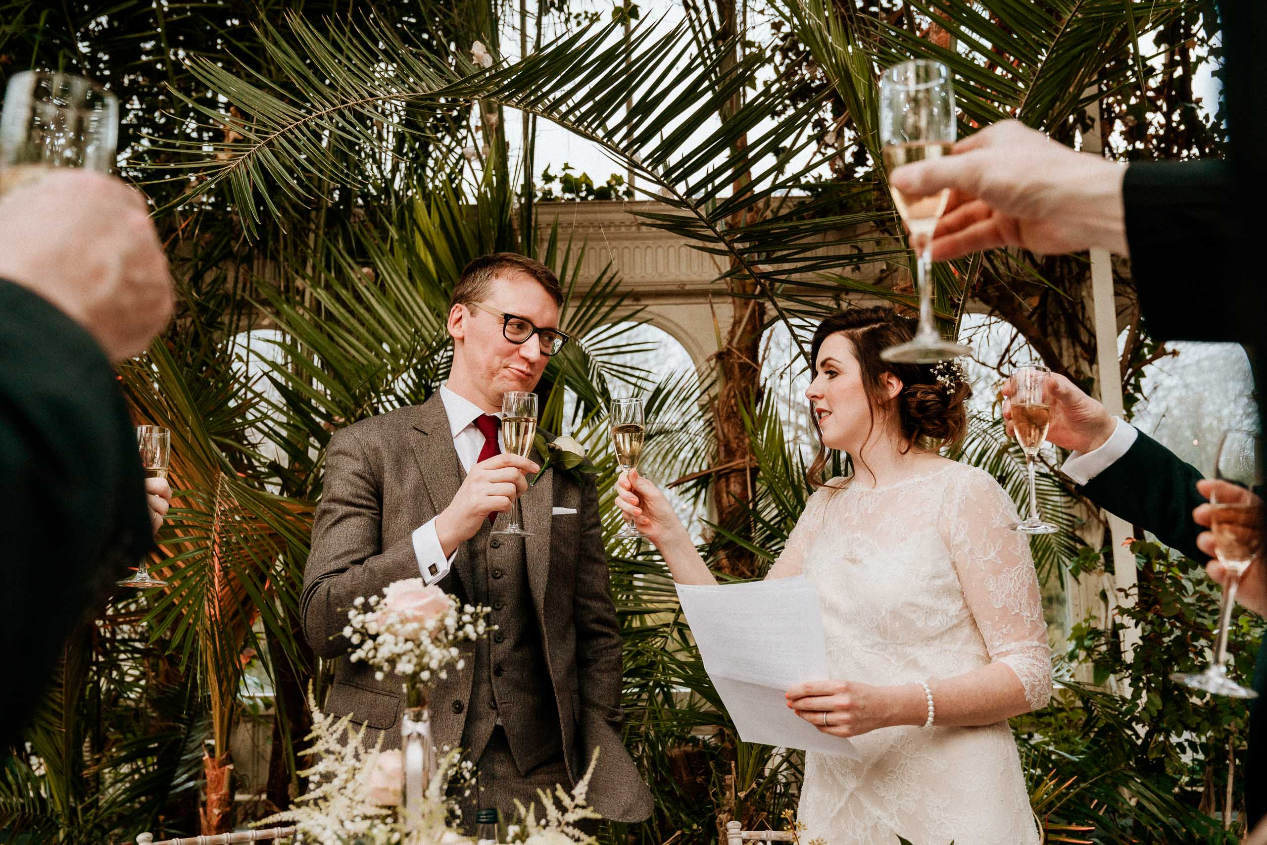 guests cheering glasses near bride and groom