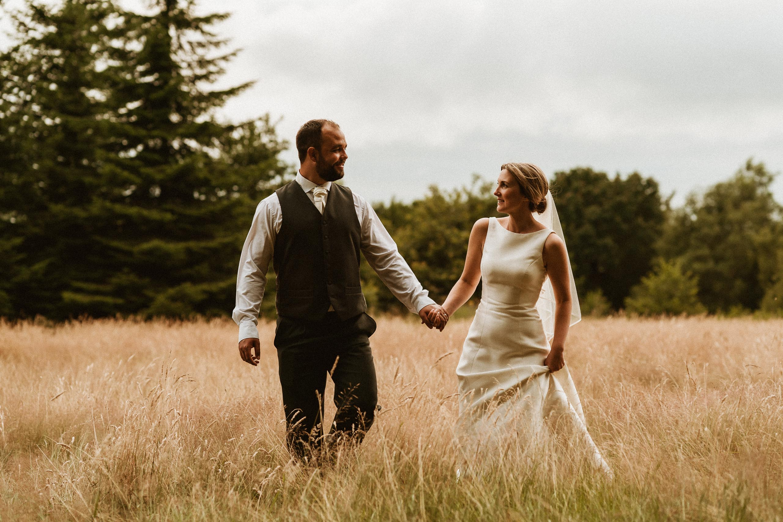 bride and groom holding hands and walking through tall grass