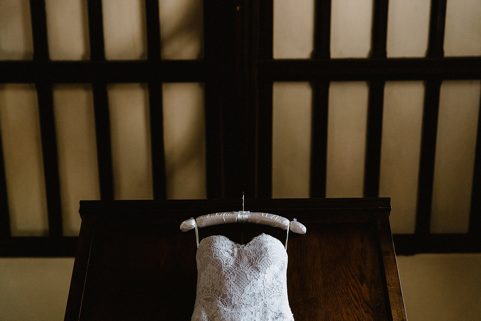 top of wedding dress hanging on dark wooden screen