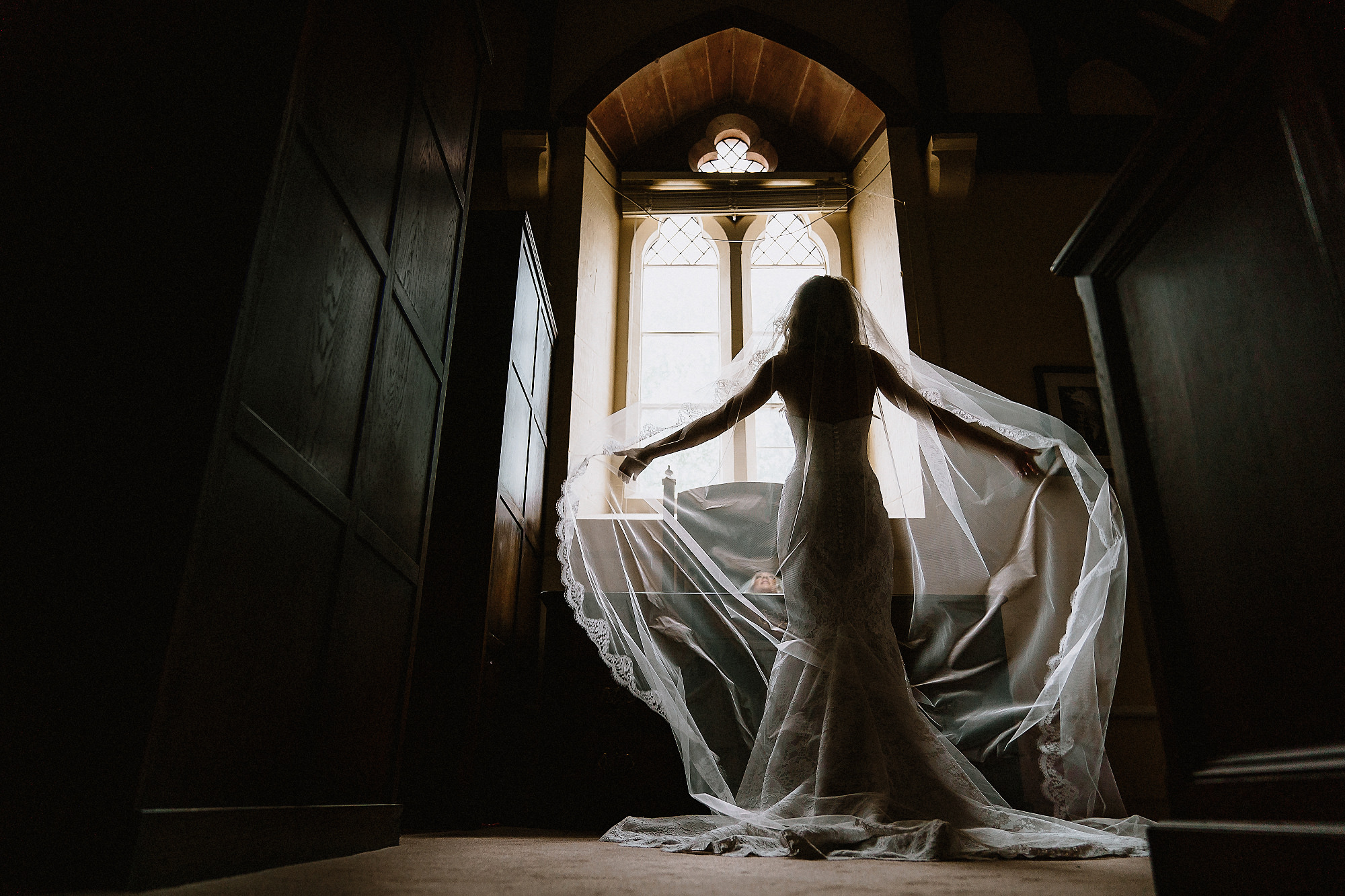 bride fluffs her wedding veil inside Peckforton Castle