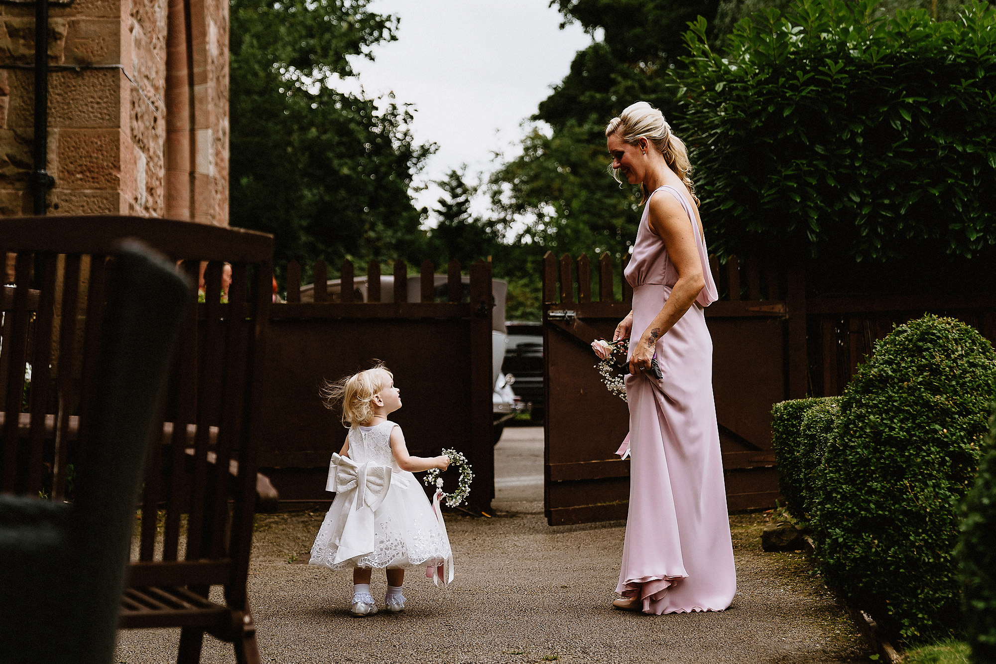 small flower girl looks up at bridesmaid
