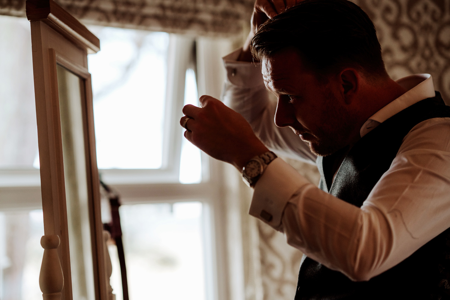 groomsman combing his hair and looking into mirror