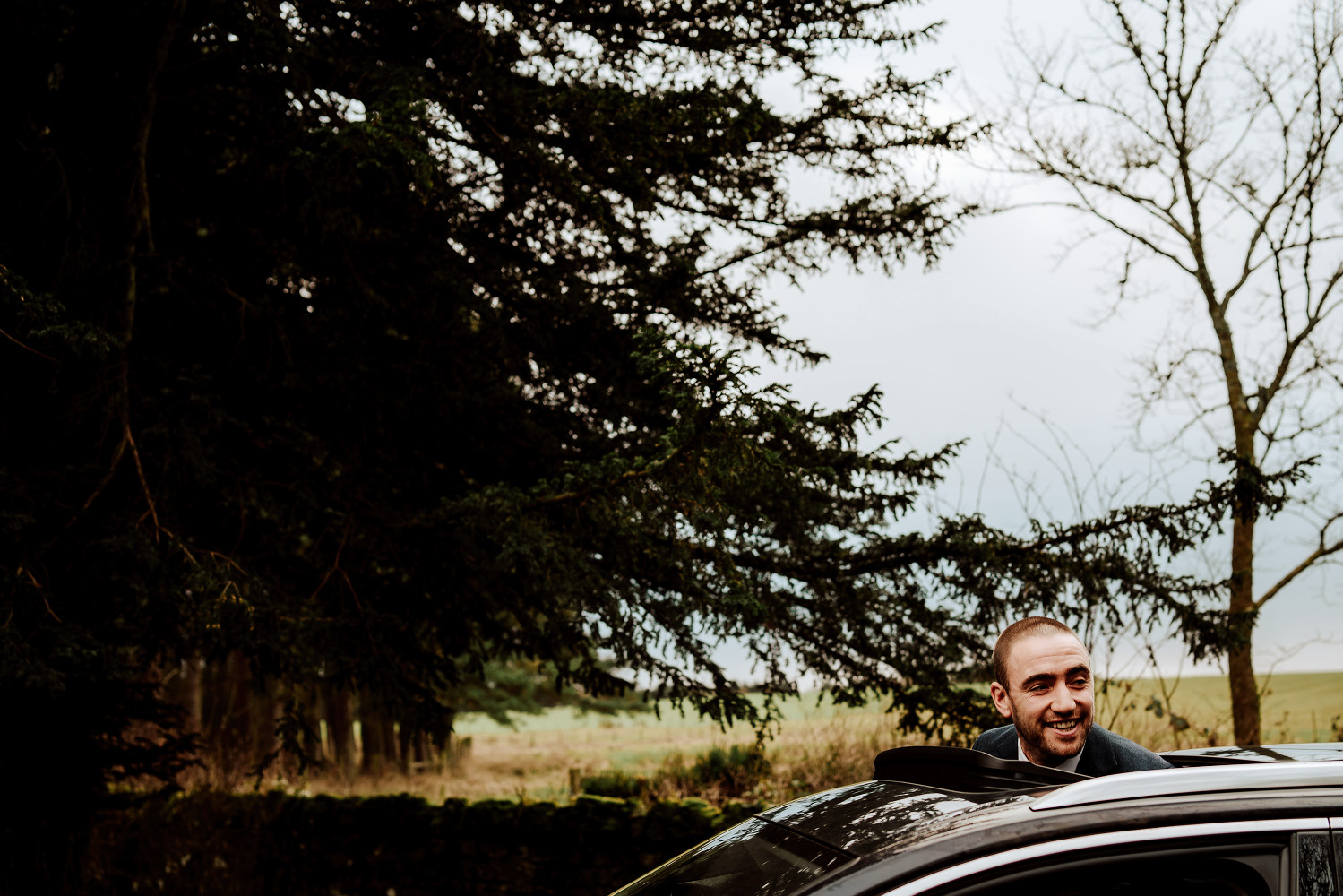 groomsman sticks his head out of car sunroof