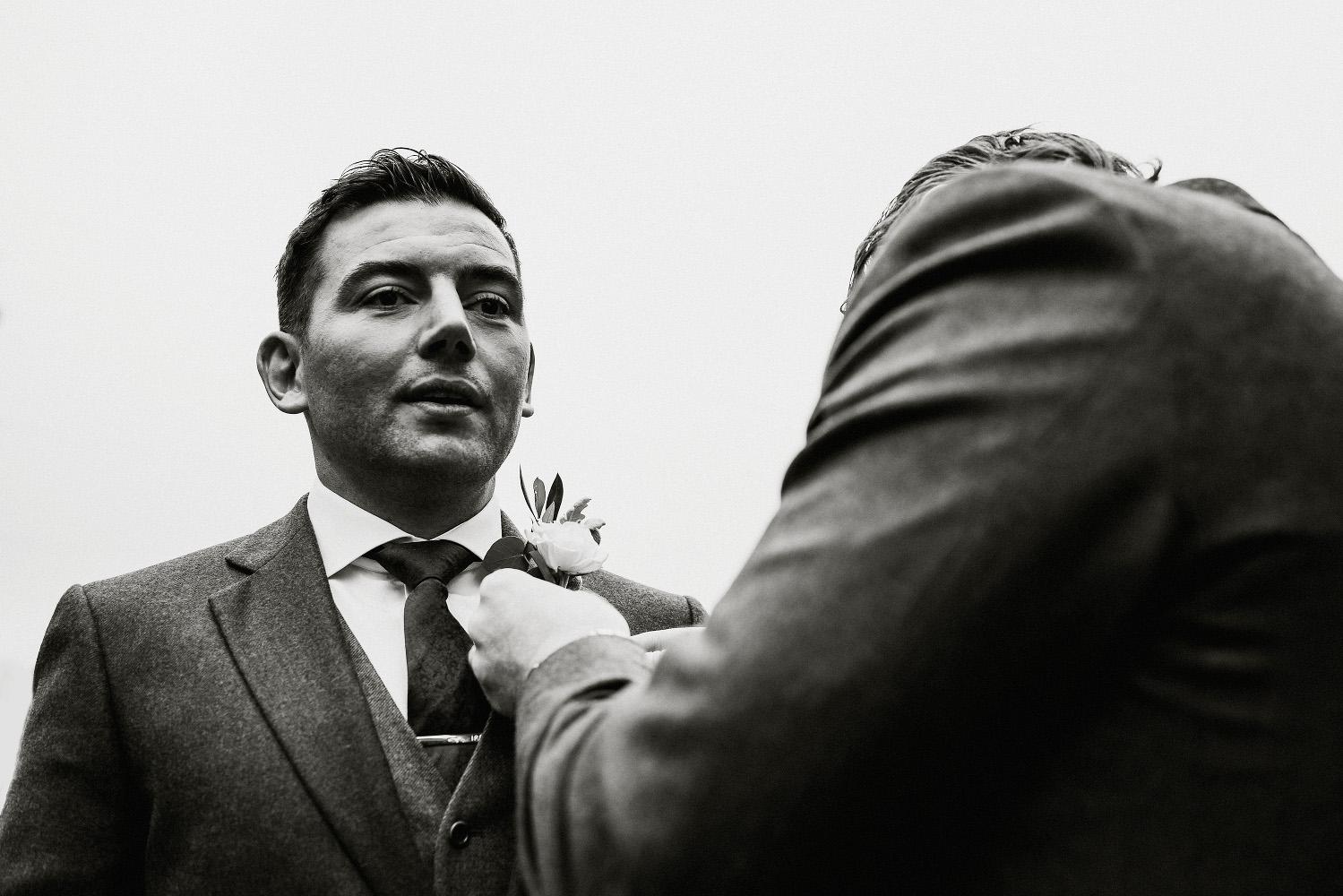 groomsman adjusts the grooms buttonhole