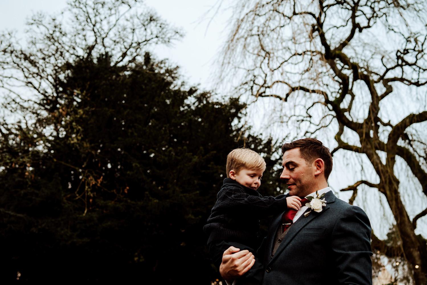 pageboy being held by groom