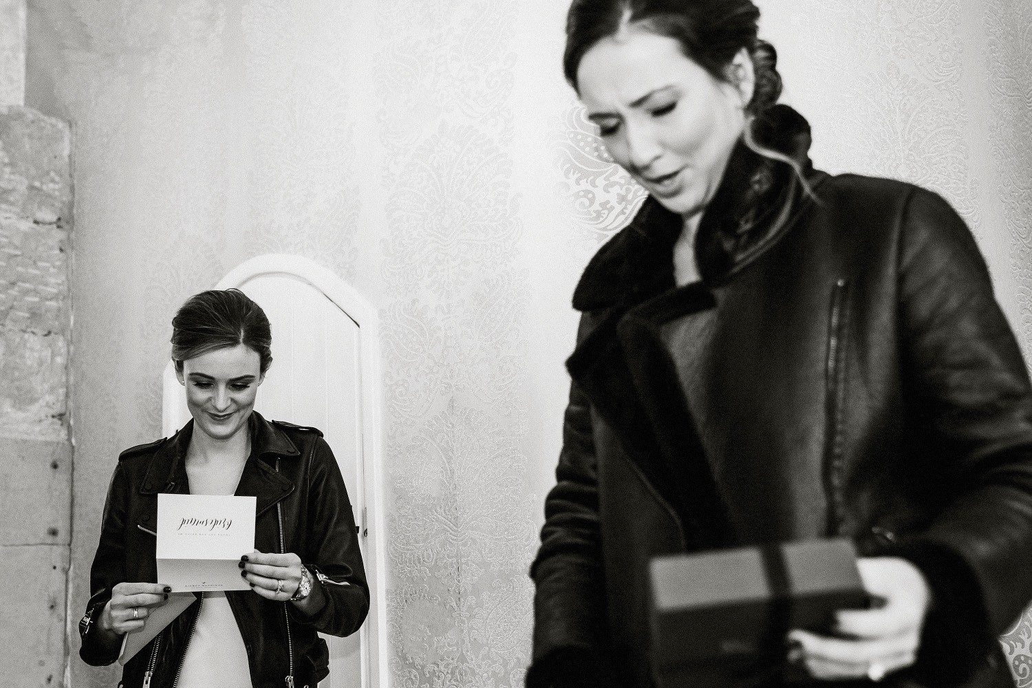 bridesmaid in leather jacket reads card
