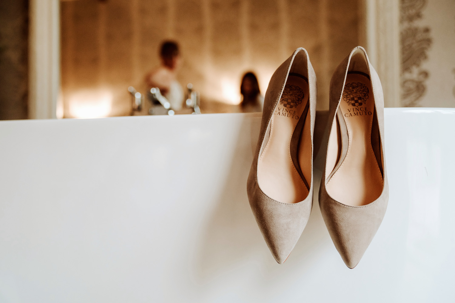 Vince Camuto wedding shoes hanging on edge of bath
