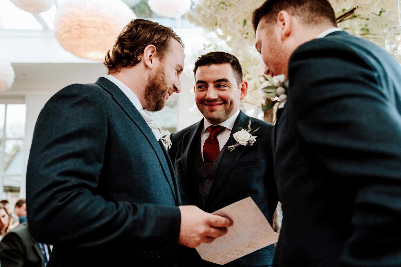 groom and groomsmen sharing smiles in ceremony room