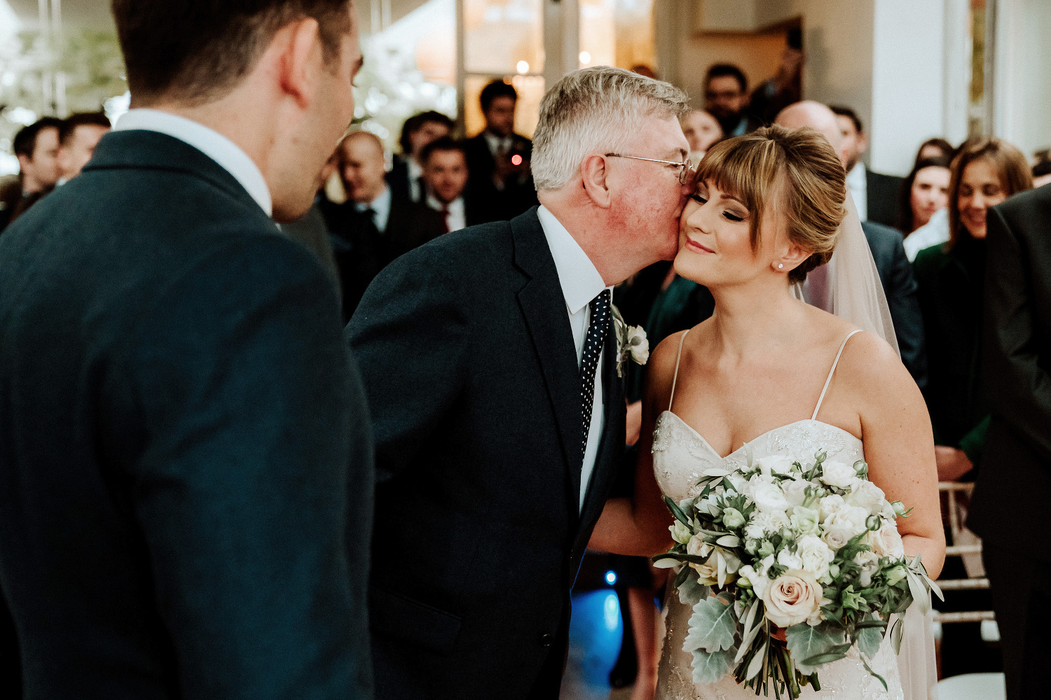 father of the bride kisses bride on cheek