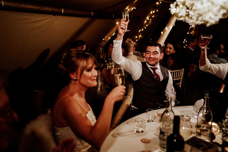 groom raises toast to bride