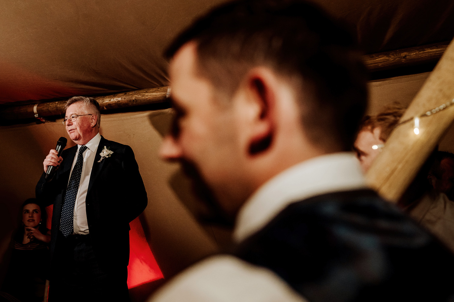father of the bride with microphone watched by groom