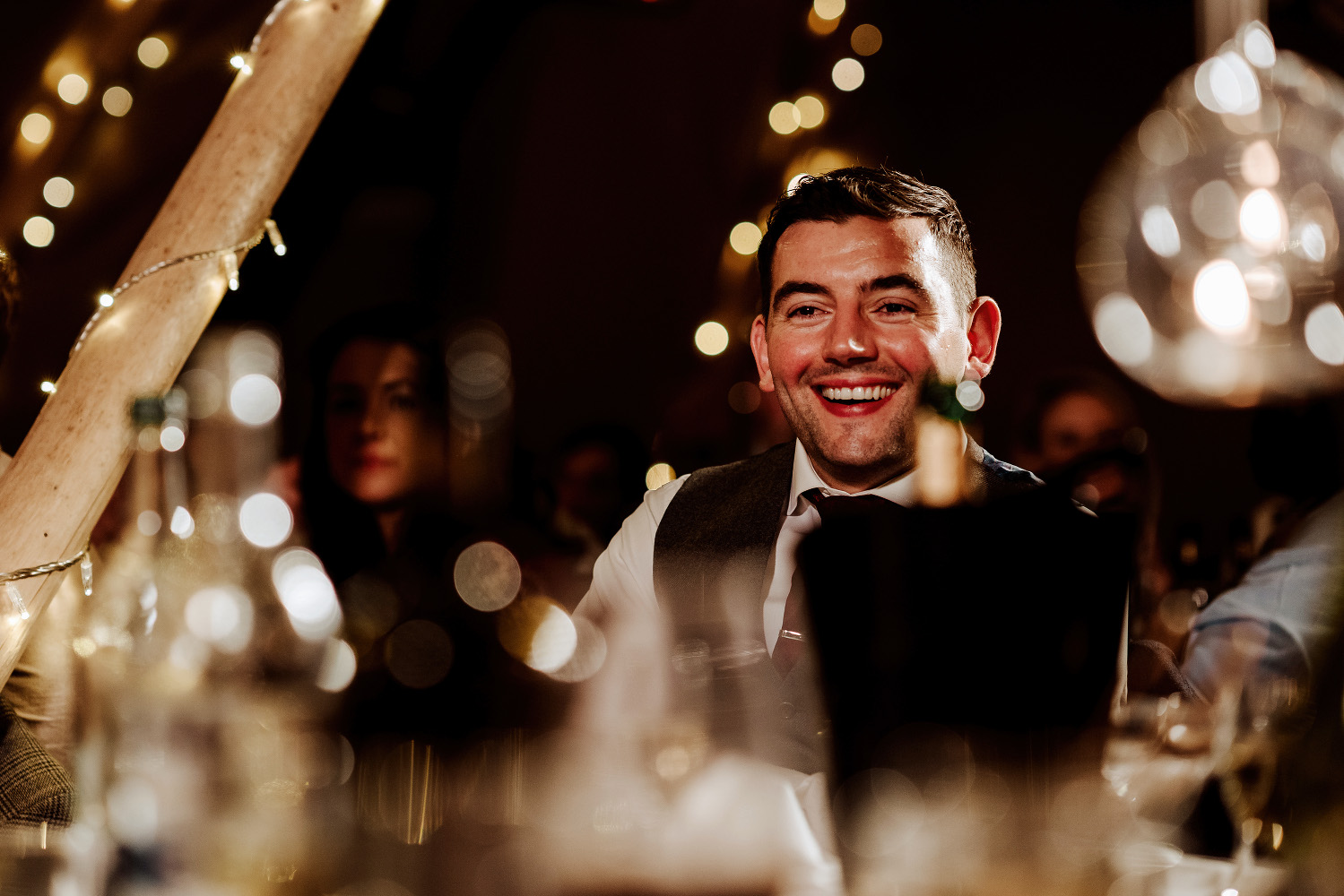 groom sits at top table with bottle of champagne