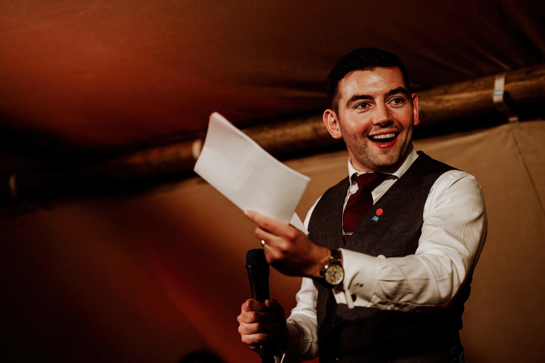 groom in waistcoat smiles and waves handwritten speech