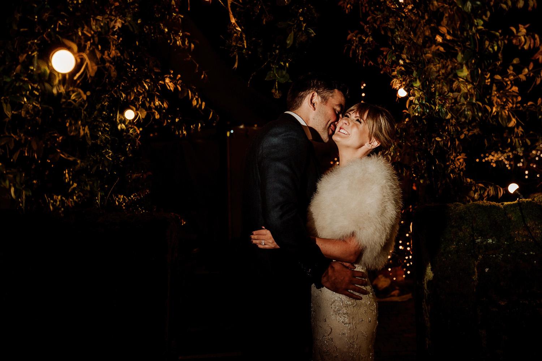 bride and groom hug under leaf arch