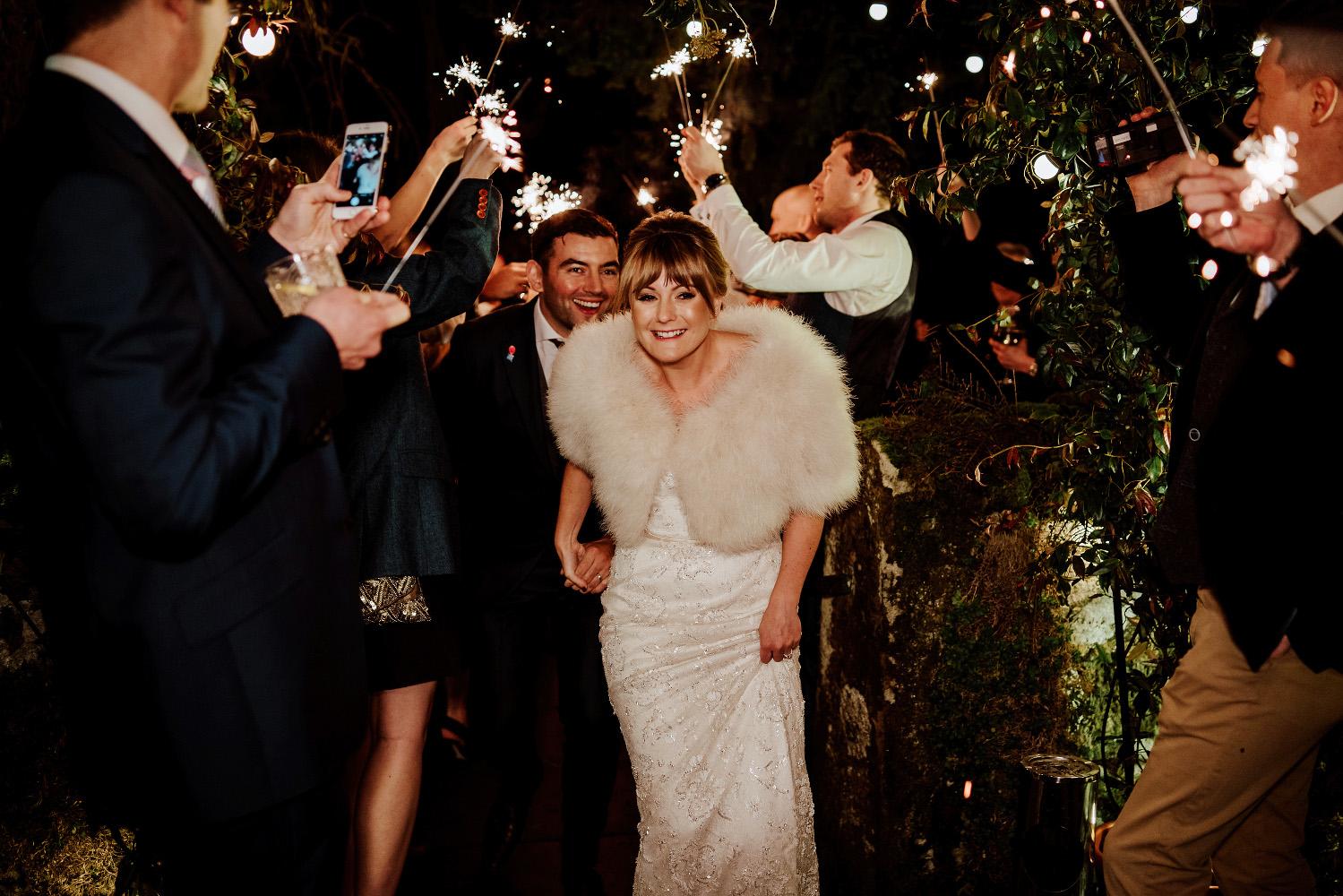 bride ducks under sparklers