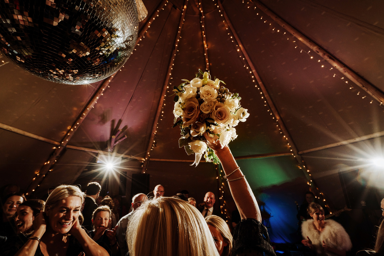 hand rises up to catch bridal bouquet