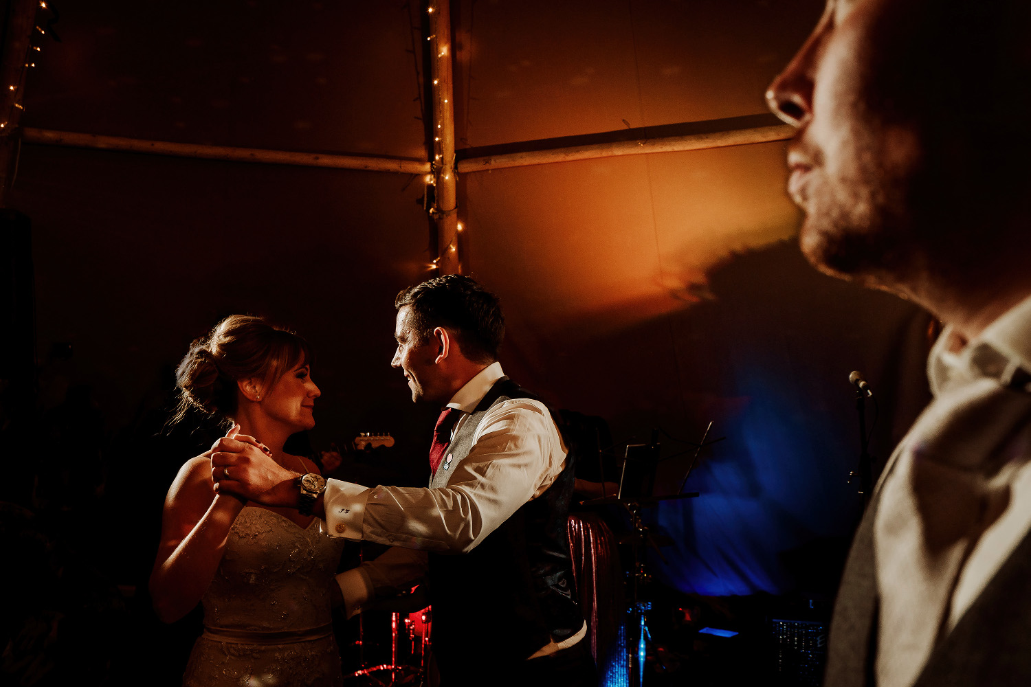 bride and groom dancing as best man watches