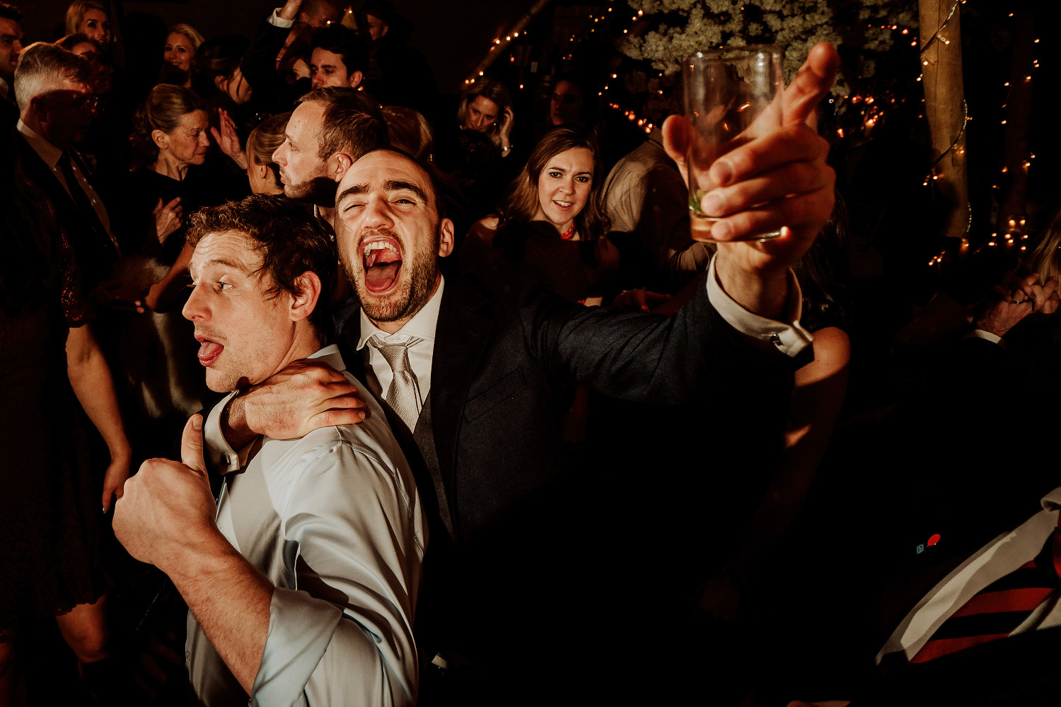 male wedding guest cheering and raising glass