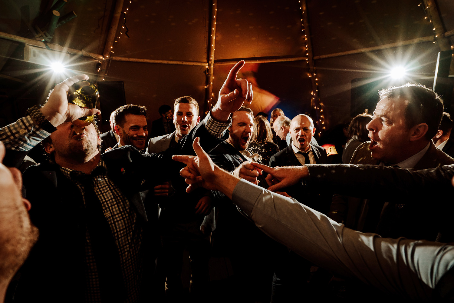 wedding guests pointing at man drinking beer