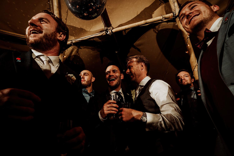 grinning groomsmen watching first dance