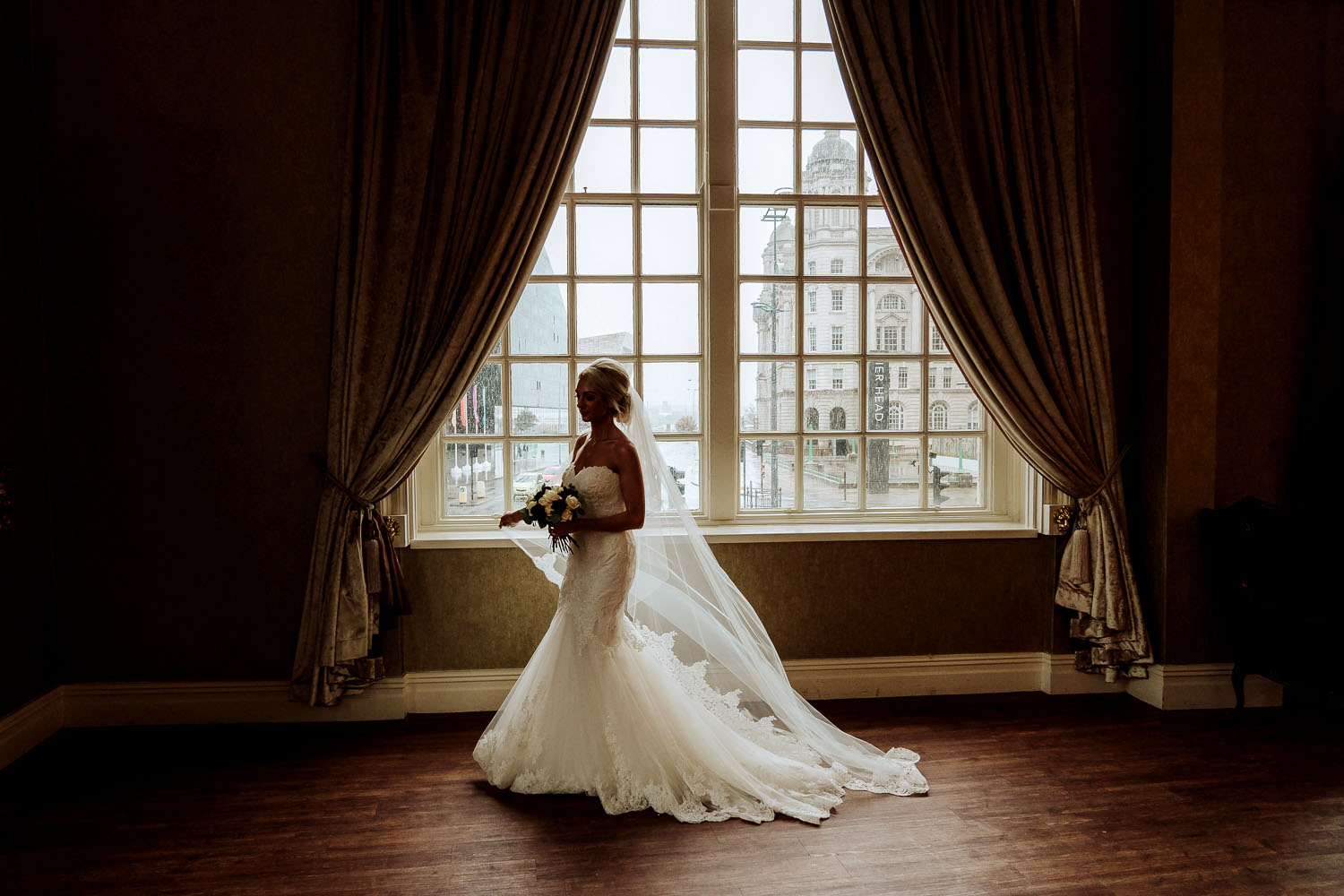 bride beneath grand window